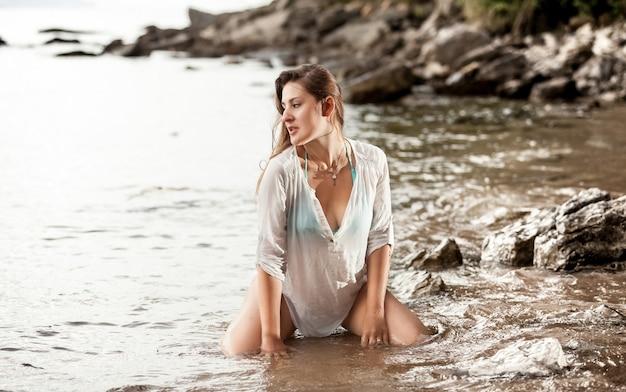 Belle photo de femme élégante sexy assise dans l'eau au bord de la mer