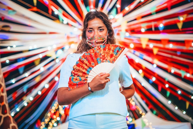 Belle photo de femme européenne bronzée portant un masque floral dans un parc d'attractions