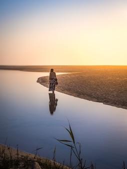 Belle photo d'une femme marchant sur la plage pendant le coucher du soleil