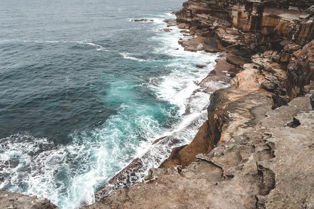 Belle photo d'une grande falaise à côté de l'eau bleue un jour sombre