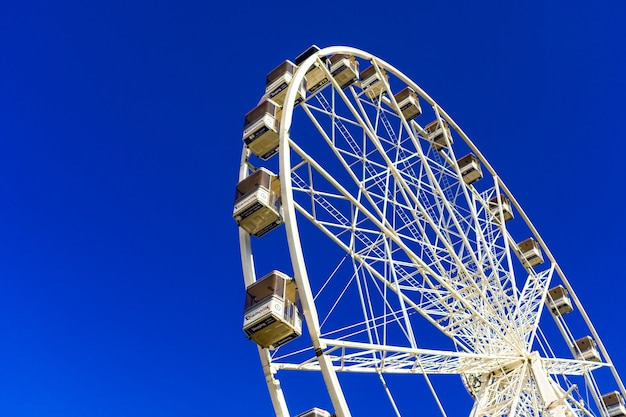 Belle photo d'une grande roue sur le parc d'attractions contre le ciel bleu