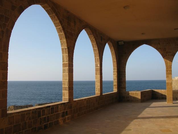 Belle photo d'une grande terrasse avec des arches en pierre avec vue sur un paysage marin