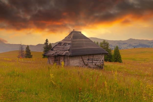 Belle photo de la grange sur les champs d'herbe pendant le coucher du soleil