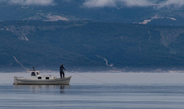 Belle photo d'un homme sur un bateau attrapant du poisson dans le lac avec des montagnes en arrière-plan