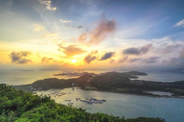 Belle photo d'une île entourée de mer sous un ciel nuageux au coucher du soleil