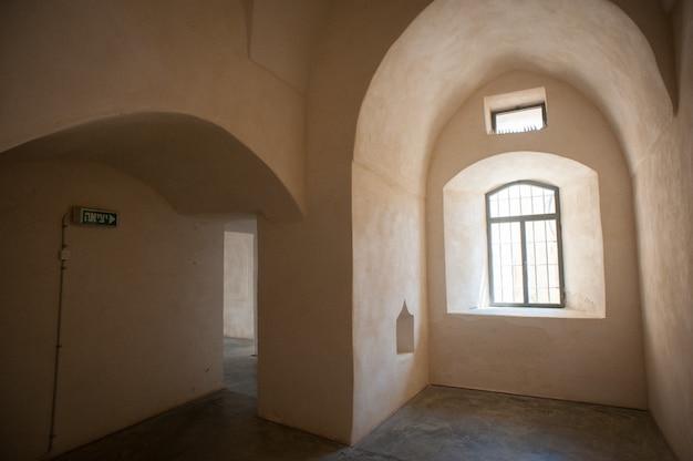 Belle photo d'un intérieur de bâtiment vide avec des fenêtres murs beiges et un panneau de sortie