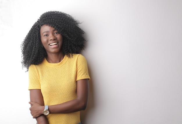 Belle photo d'une jeune femme aux cheveux bouclés isolé sur fond gris