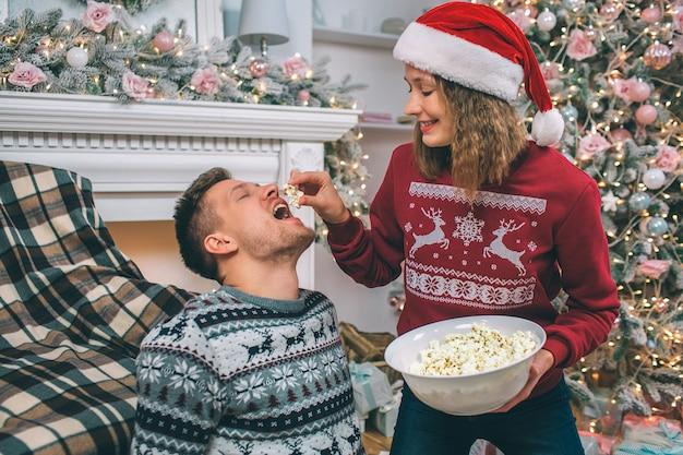 Belle photo de jeune femme se tient debout et nourrit son petit ami. elle tient un morceau de pop-corn au-dessus de sa bouche. guy garde la bouche ouverte. jeune homme est assis sur le sol.