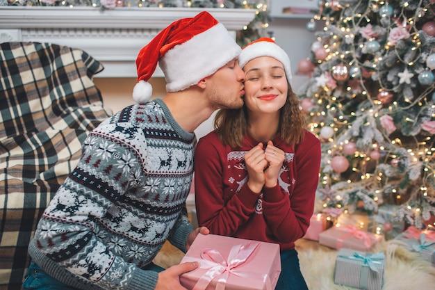 Belle photo de jeune homme embrassant une femme. elle garde les yeux fermés et les poings ensemble. elle aime ça. l'homme a présent dans les mains. le couple est dans une chambre décorée.