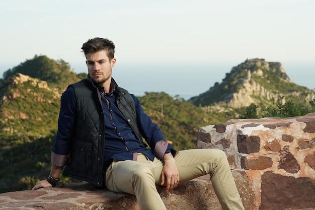 Belle photo d'un joli mâle assis confortablement devant sa maison