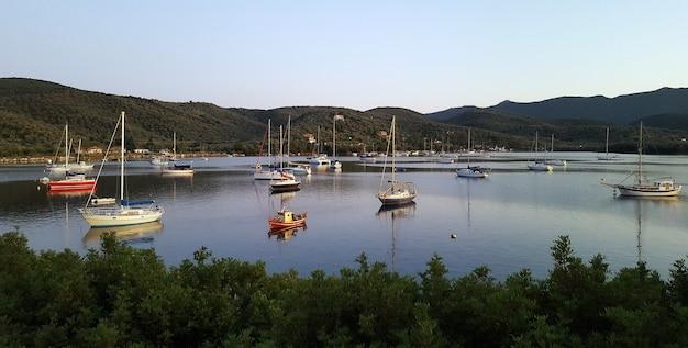Belle photo d'un lac avec des bateaux entourés de montagnes et d'arbres
