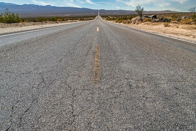Belle photo d'une longue route en béton droite entre le champ du désert