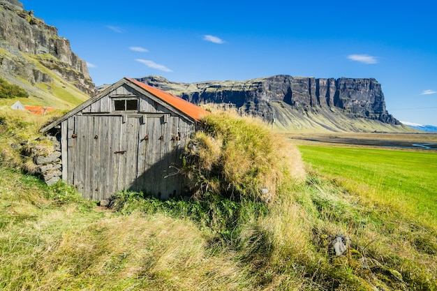 Belle photo d'une maison en bois sur un champ en islande