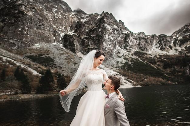 Belle photo de mariage, l'époux entoure sa jeune épouse, au bord du lac morskie oko, pologne