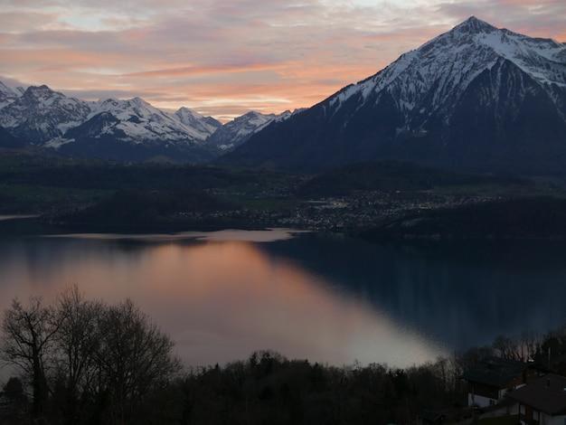 Belle photo d'une montagne escarpée avec de la neige blanche sur le sommet avec un paysage de coucher de soleil dans le ciel