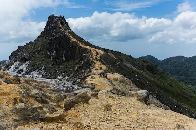 Belle photo d'une montagne sous un ciel bleu nuageux