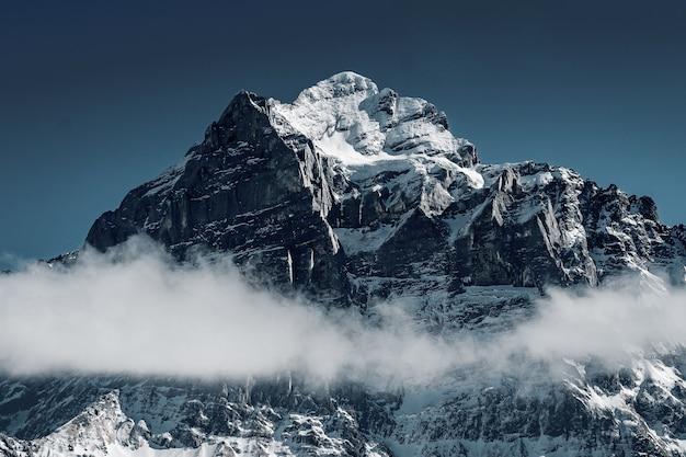 Belle photo des montagnes enneigées entourées de nuages