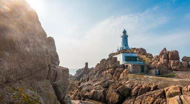 Belle photo panoramique de falaises avec un phare et une mer calme