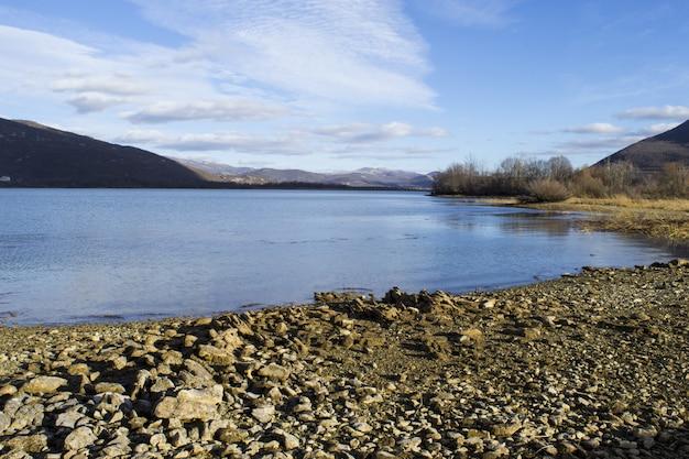 Belle photo panoramique d'un rivage serein pierreux sous un ciel bleu nuageux