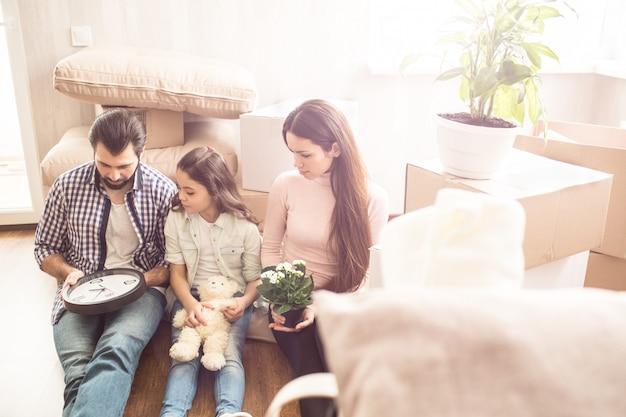 Belle photo de parents avec leur enfant assis sur le sol dans la chambre et regardant l'horloge que l'homme tient. il veut que ça marche. jeune femme tient un pot avec des plantes dans ses mains.