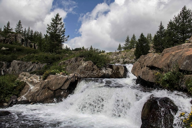 Belle photo d'une petite cascade avec des formations rocheuses et des arbres autour d'elle par temps nuageux