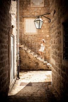 Belle photo sur la rue étroite de la jeune femme debout sur des escaliers en pierre