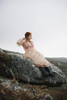 Belle photo verticale d'une femme au gingembre avec une peau d'un blanc pur dans une jolie robe rose