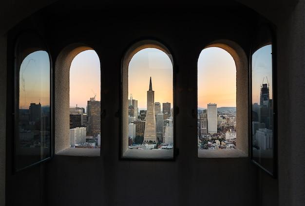 Belle photographie du coucher de soleil du centre-ville de san francisco à travers la fenêtre