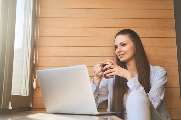 Belle pigiste heureuse de jeune femme avec une tasse dans sa main s'asseyant à un ordinateur