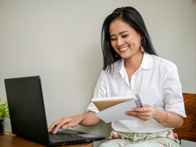 Belle pigiste tenant un livre à la main, en tapant sur un ordinateur portable