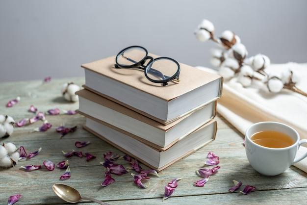 Une belle pile de livres avec des couvertures de papier craft sur une table en bois bleu