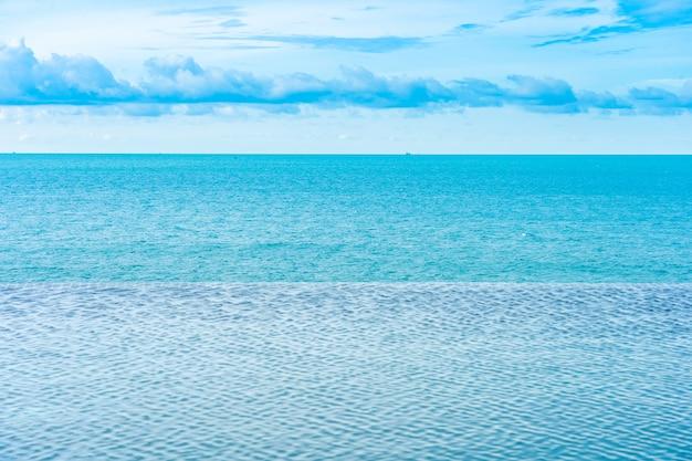 Belle piscine à débordement extérieure dans un complexe hôtelier avec vue sur la mer, océan et nuage blanc, ciel bleu