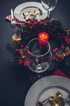 Belle place de dîner de noël pour deux. table décorée d'une guirlande et d'une bougie.