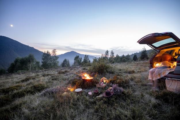 Belle place de pique-nique près du coffre de la voiture avec un feu de camp dans les montagnes le soir au crépuscule