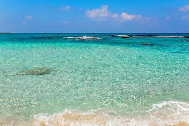 Belle plage aux eaux bleues cristallines contre le ciel bleu