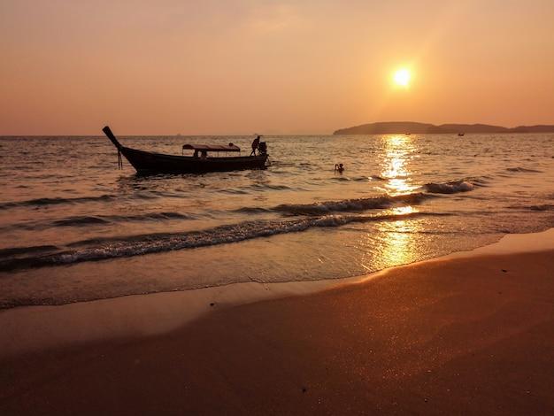 Belle plage avec bateau dans l'eau au coucher du soleil