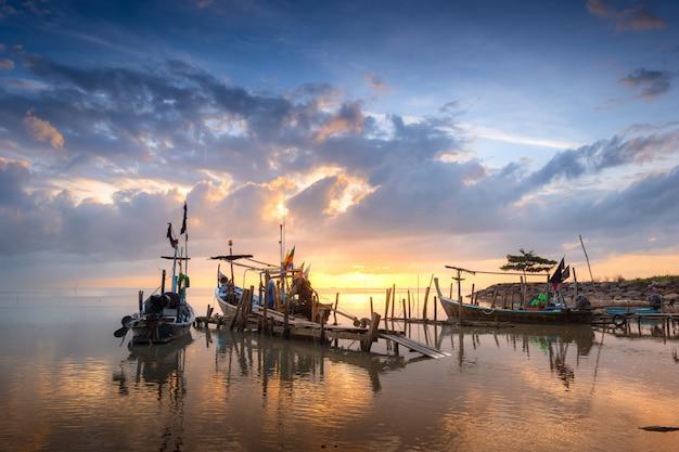 Belle plage avec bateau de pêcheur au lever du soleil.