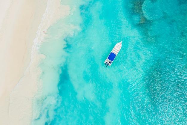 Belle plage des caraïbes sur l'île de saona, république dominicaine. vue aérienne abstraite du paysage d'été idyllique tropical avec de l'eau de mer bleue, du sable blanc et un seul bateau