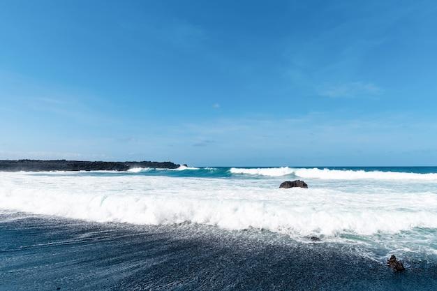 Belle plage sur l'île de lanzarote. plage de sable entourée de montagnes volcaniques / océan atlantique et magnifique plage. lanzarote. les îles canaries