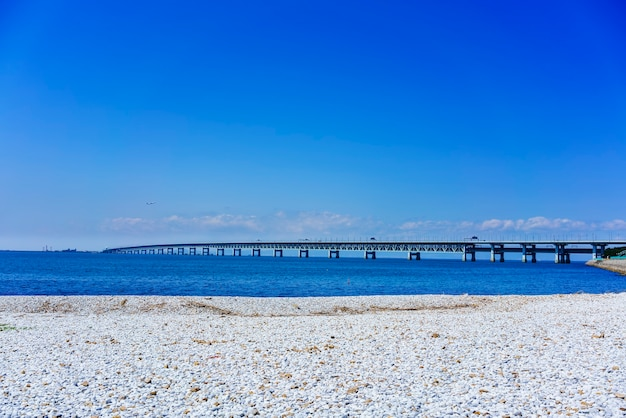 Belle plage de marbre artificielle le long du rivage de la ville de rinku, vue sur kansai kokusai kuko renraku-kyo (route à péage) à travers la mer bleue de la baie d'osaka jusqu'à l'aéroport international de kansai, osaka, japon