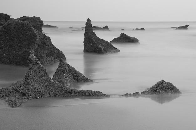 Belle plage en noir et blanc avec la mer et ses vagues calmes.