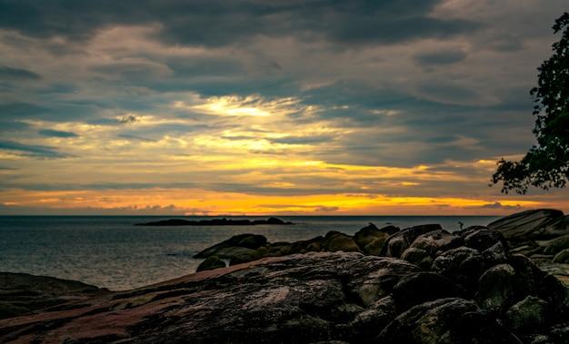 Belle plage de pierres le matin avec un ciel doré au lever du soleil. scène paisible et tranquille. paysage de mer calme le matin. paysage marin avec skyline. mer tropicale. beauté dans la nature.