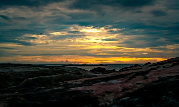 Belle plage de pierres le matin avec un ciel doré au lever du soleil. scène paisible et tranquille. paysage de mer calme le matin. paysage marin avec skyline. mer tropicale.