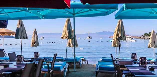 Belle plage sur les rives de la baie bleue calme de la mer égée au coucher du soleil et des vacances à la plage