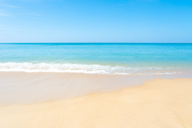 Belle plage de sable fin et mer tropicale avec un ciel bleu en jour d'été.