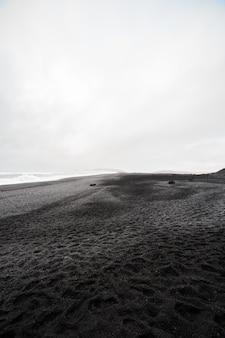 Belle plage de sable noir volcanique à dyrholaey, en islande.