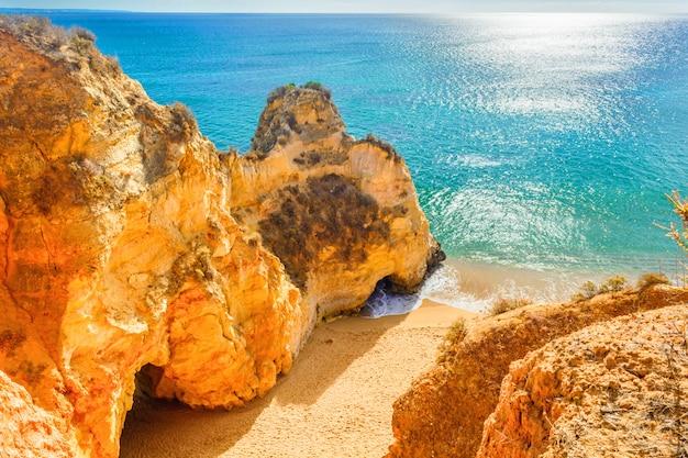 Belle plage de sable parmi les rochers et les falaises près de lagos, algarve, portugal