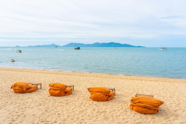 Belle plage tropicale mer et océan avec cocotier, parasol et chaise sur ciel bleu et nuage blanc