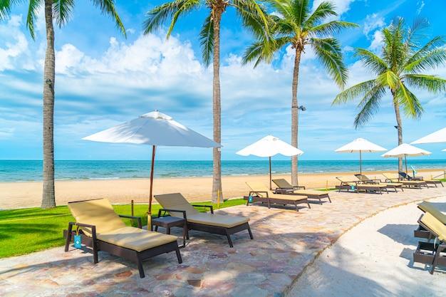 Belle plage tropicale et mer avec parasol et chaise autour de la piscine dans la station de l'hôtel