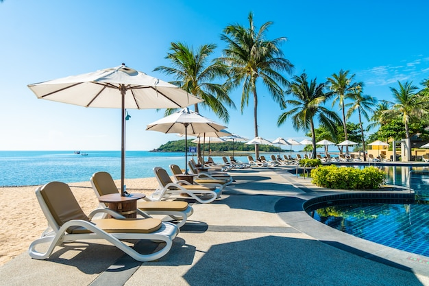 Belle plage tropicale et la mer avec parasol et chaise autour de la piscine